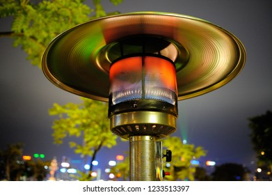 Close up at radiant outdoor gas heater working at night in the street restaurant. Green-orange toned reflections. Tree and buildings in background.
