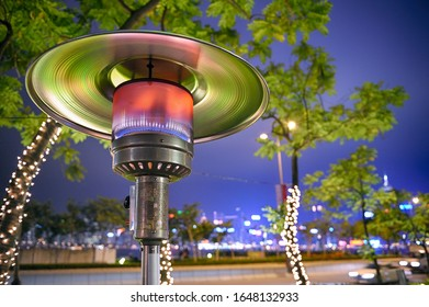 Close up at radiant outdoor gas heater at night in the street restaurant. Green-orange toned reflections. City lights in background.