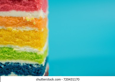 Close up of rainbow layer cake in blue background