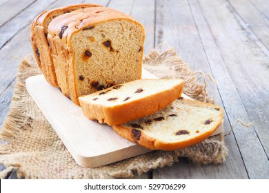 Close up of raisin cinnamon  sliced loaf on a wooden table.