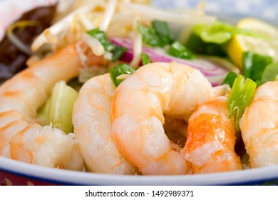 Close up ramen soup with shrimp in traditional Asian bowl and red plate isolated on white background.