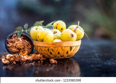 Close up of raw amla or Phyllanthus emblica or Indian gooseberry in a fruit basket with its dried seed powder in a clay bowl used in face pack,drinks and in natural medicines on wooden surface.;