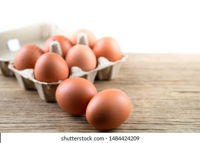 Close up of raw chicken eggs in egg box, organic food from natural on rustic wood table isolated on white background