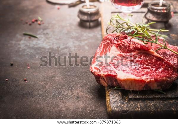 Nahaufnahme von rohem frischem Fleisch Ribeye Steak mit Kräuter und Gewürzen auf dunklem rustikalem Metallhintergrund, Ort für Text.