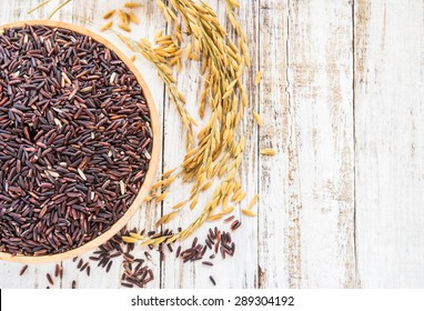 Close up raw purple rice berry in wooden bowl on white wooden background