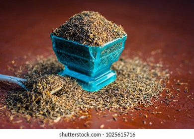 Close up of raw shah zeera or shah jeera,Carum carvi,caraway seeds in a blue bowl on brown wooden surface.
