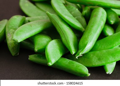 Close up of raw sugar snap peas on a black background