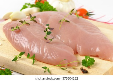 close up of raw turkey breasts with vegetables, spice and herbs on wooden cutting board