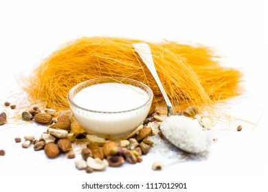 Close up of Raw vermicelli or sevee or seviyan or seviyaan and dry fruits isolated on white with a bowl of milk used to make kheer.