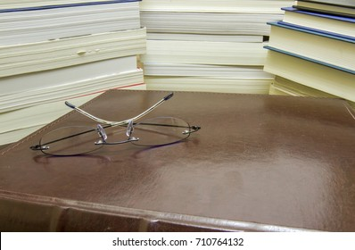 Close up of reading glasses on leather book next to piles of paperback and hardback novels.