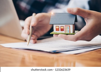 Close up real estate agent with house model hand putting signing contract, signing of modest agreements form in office. Concept real estate, moving home or renting property