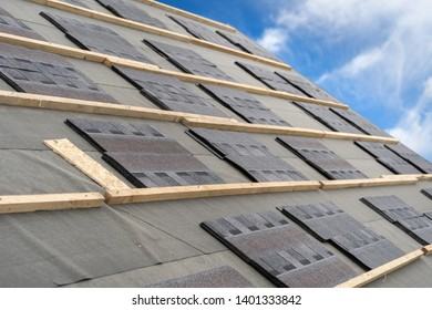 Close up and real photo element of layer on installing asphalt or bitumen shingle on top of the new roof under construction residential house or building against beautiful blue sky on background