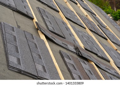 Close up and real photo of layer of installing asphalt or bitumen shingle on top of the new roof under construction residential house or building