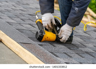 Close up and real photo of professional workman in protective uniform using air or pneumatic nail gun and installing asphalt or bitumen tile on top of the roof under construction house