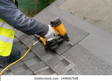 Close up and real photo of unrecognizable workman in protective uniform using air or pneumatic nail gun and installing asphalt or bitumen tile on top of the roof under construction house