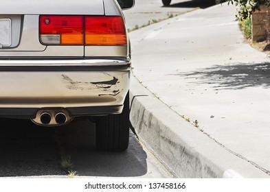 Close up of a rear car bumper side swiped.