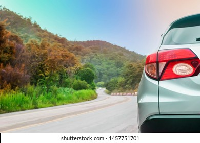 Close up rear of new silver car with tail lights parked on street at parking lane while driving pass through the forest and mountain, safety travel holiday transportation with car in nature concept