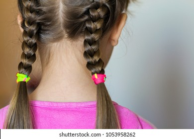Close up rear- vew portrait of a cute little girl with funny pigtails on white background. Fashion and happy childhood.