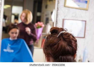 Close Up Rear View of Brunette Woman Sitting in Salon Chair with Hair Clipped Up While Stylist Works on Style in Salon with Reflection in Large Mirror in Background