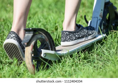 Close up rear view of child riding kick scooter, green grass on summer meadow