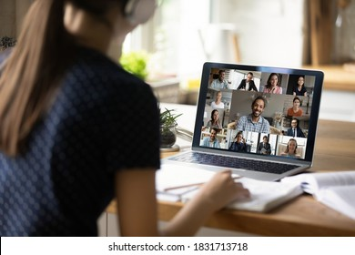 Close up rear view of female student study distant at home on computer, engaged in group webcam lecture or lesson. Woman speak talk on video call with diverse colleagues, have online team meeting.