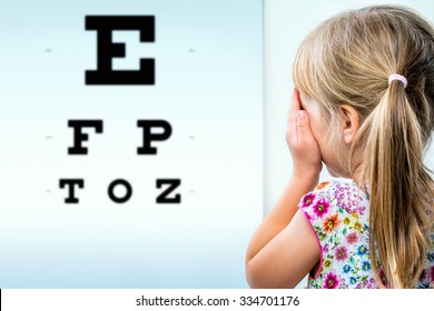 Close up rear view of girl testing eyesight. Infant closing one eye with hand looking at vision test chart.