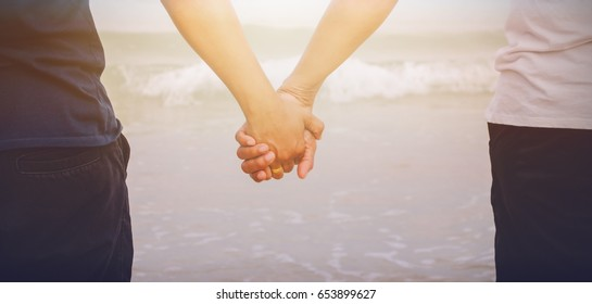Close up of  rear view of a romantic senior Couple holding hands walk together at the beach. Honeymoon concept.
