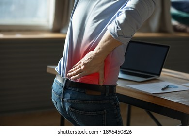 Close up rear view stressed young man touching lower back feeling discomfort, suffering from sudden pain due to sedentary lifestyle or long computer overwork in incorrect posture at home office.