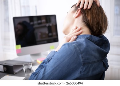Close up rear View Tired Office Woman Sitting at her Desk Massaging her Neck While Holding her Head.