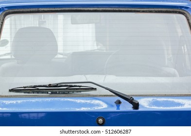 Close up of rear windshield wiper arm and blade on sun bleached blue vintage motor vehicle