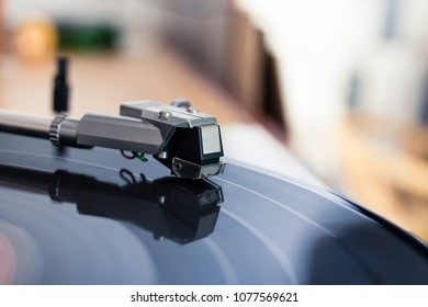 Close up of a record player stylus on a spinning vinyl disc