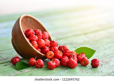 Close up Red Acerola Cherry in wooden bowl on green wood background, High vitamin C and anti oxidant fruits.
