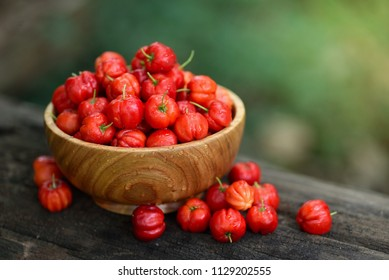 Close up Red Acerola Cherry in wooden bowl with water drops and green blur background, High vitamin C and antioxidant fruits.