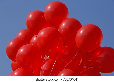 close up of red air balloons against blue sky