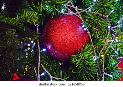 close up of red ball with colorful decorative light on Christmas tree