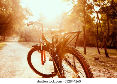 Close up of a red and black mountain bicycle with morning sun.