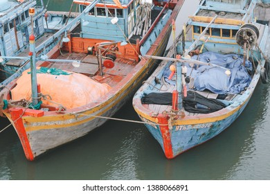 Close up red and blue wooden boats smacks mooring in Binh Thuan, Vietnam