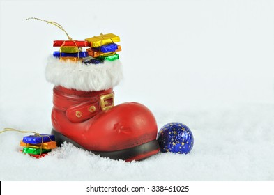 close up of a red boot with white fur trimming, filled with sweets, on white, snowy background, horizontal / St Nicholas`Day