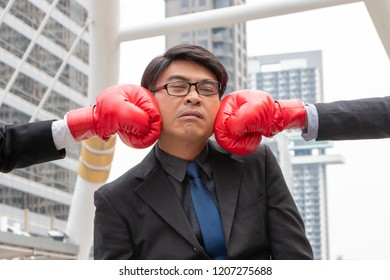 Close up red boxing gloves of competitors punching Asian businessman in his face in modern city background. Businessman is defeated in the competition game. Business and competition concept.