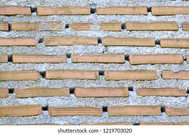 Close up red brick wall with blowholes and rough concrete for background texture