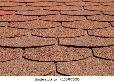 Close up of red brown curved shingles of roof in perspective. Textured background. Copy space