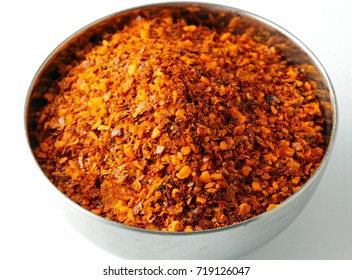 Close up of red chili powder in a steel isolated on white background.