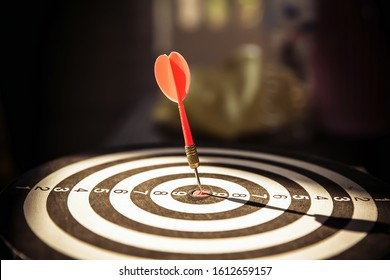 Close up red color arrow in the center of Bullseye with dark background concept of business goal, genius and capability.