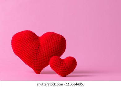 close up red of crochet heart shape isolated on pink color background