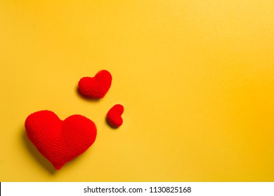 close up red of crochet heart shape isolated on yellow color background
