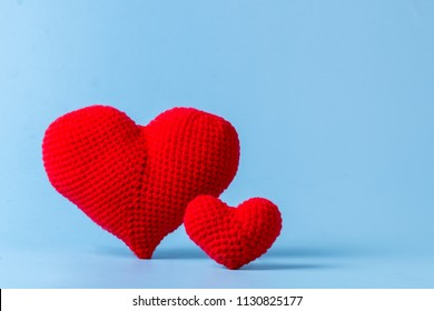 close up red of crochet heart shape isolated on blue color background
