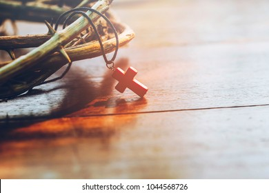 close up of  the red cross hang on crown of thorns of Jesus on  wooden background with copy space, can be used for Christian concept , Easter concept, Vintage tone