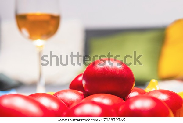 Close up of red Easter eggs, glass of wine in the background, side view. Blurry background.