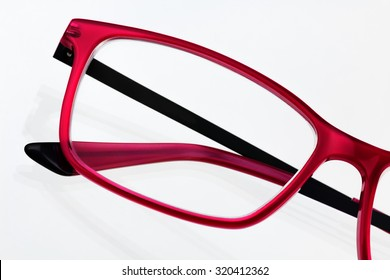 Close up of red eyeglasses frame with white background and shadows. Processed with enhanced slightly gritty tones.