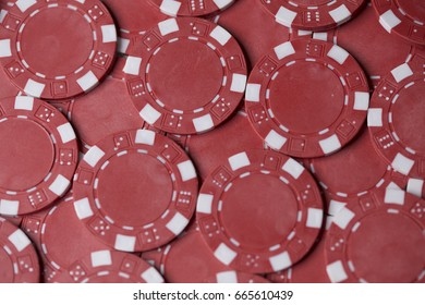 Close up of red gaming chips spread out to fill the frame thereby creating a background